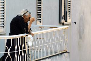 signora molto anziana guarda dal balcone