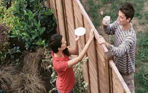 ragazza parla col vicino di casa che si trova al di là di un recinto