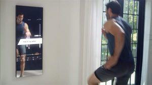 uomo si allena di fronte a uno specchio interattivo